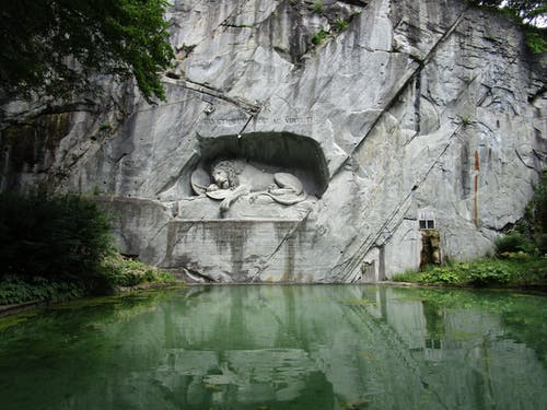 Gray Lion Statue Beside Green Lake