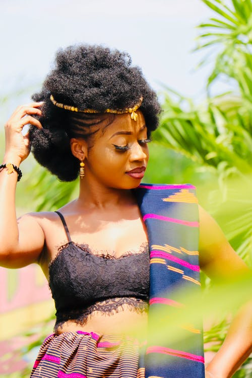 Pretty slim African American curly female with closed eyes in colourful  traditional wear posing sensually and touching hair with hand near green plants