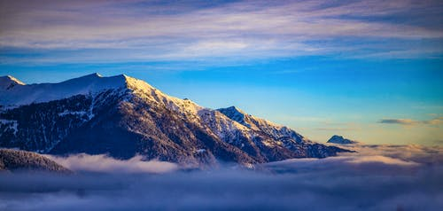 Picturesque scenery of snowy mountainous peaks with clouds under mountains