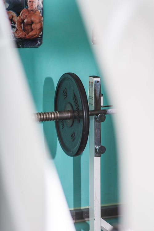 Heavy barbell on stand in modern gym