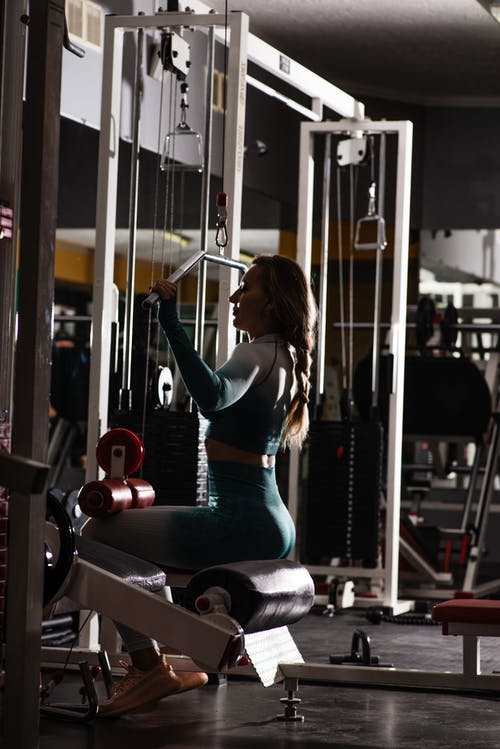 Determined sportswoman exercising on arm machine in gym