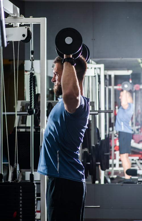 Powerful brutal sportsman in activewear lifting heavy dumbbells against big mirror while training in contemporary sports club