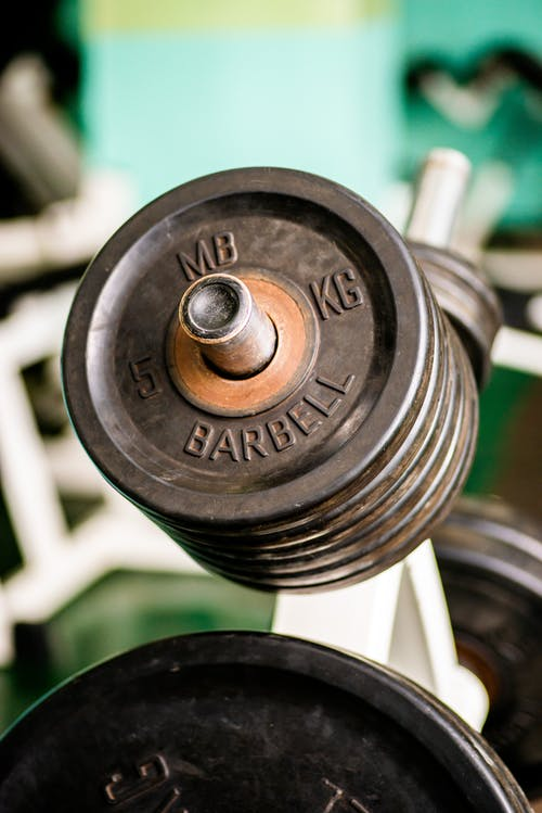 Metal weight plates placed on rack in contemporary fitness center against blurred gym equipment