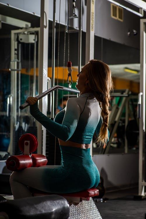 Slim sportswoman exercising on arms machine in gym
