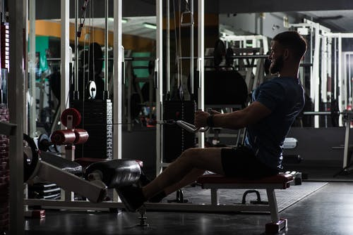 Side view full length determined focused male in sportswear sitting on rowing machine and performing arms exercise during workout in contemporary spacious fitness club