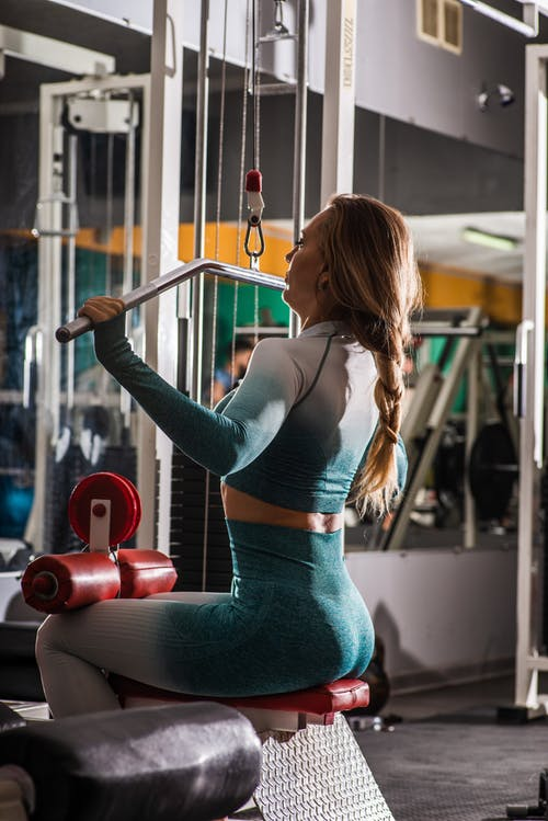 Sportswoman exercising on arms machine in fitness club