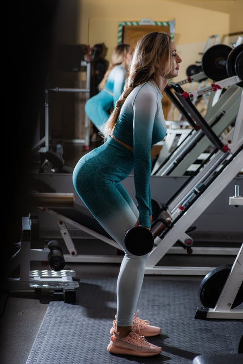 Slim sportswoman exercising with barbell in gym