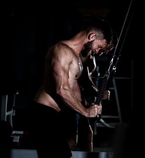 Strong bodybuilder exercising with ropes triceps extension