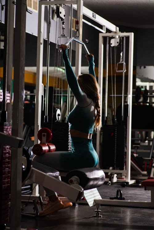 Faceless sportswoman performing arms exercise on machine in gym