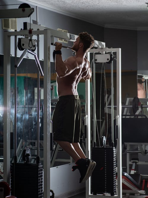 Muscular sportsman doing pull up exercise in gym