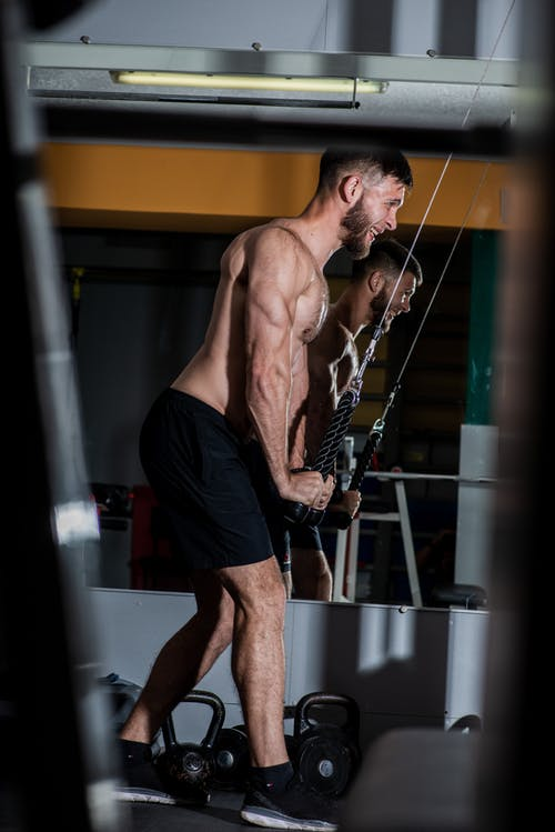Side view full length determined shirtless sportsman pulling down cable rope triceps extension during energetic workout in modern gym