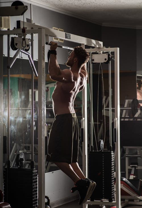 Back view full length muscular shirtless sportsman doing pull ups exercises during workout in contemporary fitness club