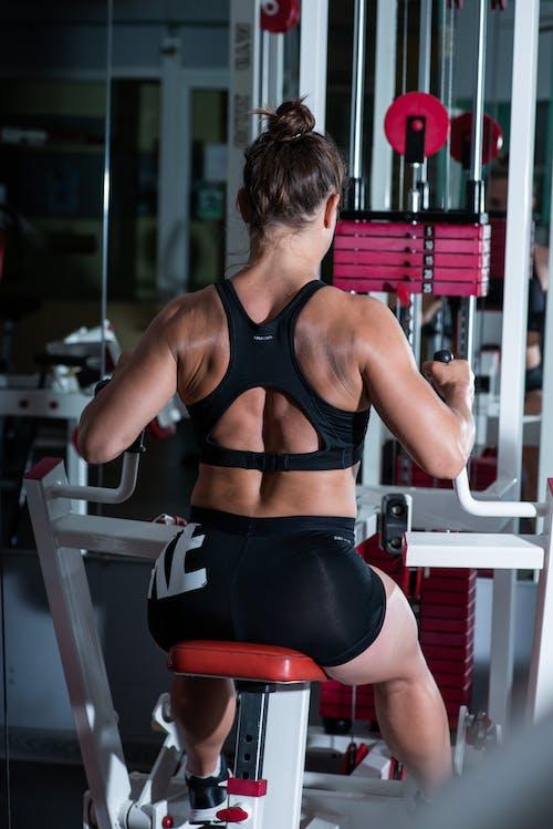 Faceless sportswoman exercising in modern gym
