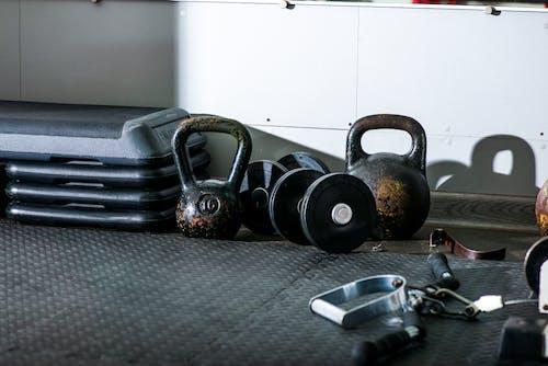 Kettle bells and dumbbells on floor near gym equipment