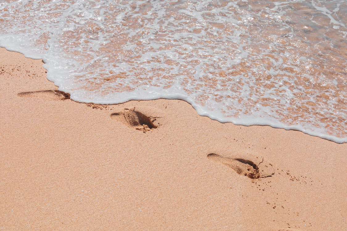 Brown Sand Near Body of Water