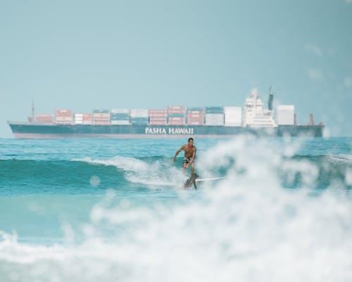 Woman in Blue Bikini Surfing on Sea