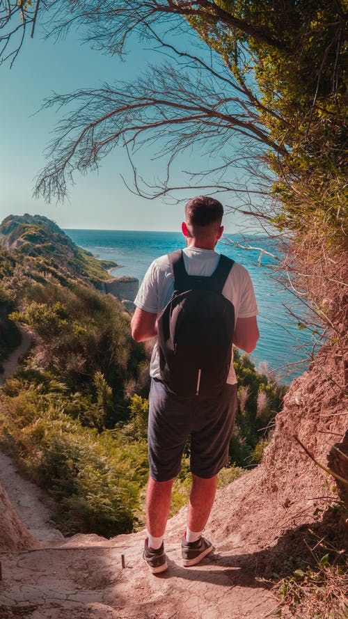 Unrecognizable male backpacker standing on cliff against blue sea