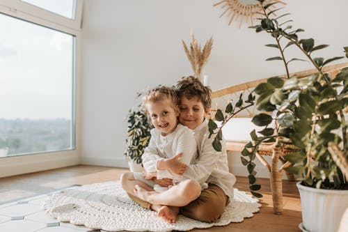 Photo of a Boy Hugging His Little Sister