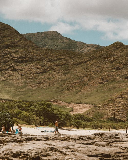 People on Beach Near Mountain