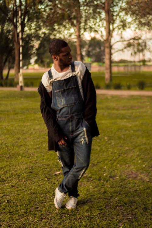 Man in Blue Denim Jacket Walking on Green Grass Field