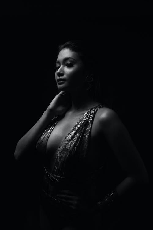 Black and white of young sensual ethnic woman in elegant wear touching neck in darkness