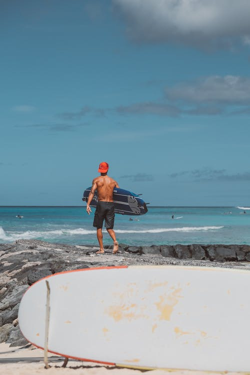 Man in Black Shorts and Black Shirt Standing on White Surfboard on Seashore