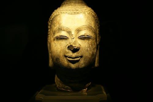 Old golden sculpture of Buddha against black background