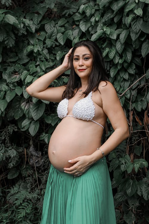 Smiling ethnic pregnant woman in summer outfit relaxing in garden