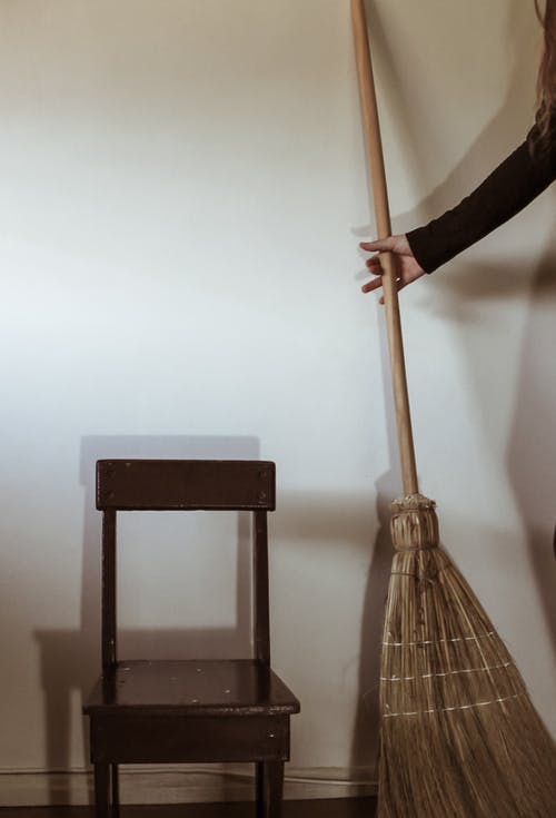 Crop anonymous female holding broom while standing near wooden chair after housework in minimalist room