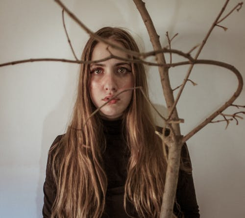 Sad young woman standing near leafless plant twigs and looking at camera