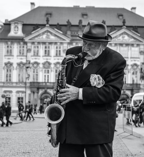 Man in Black Hat Playing Saxophone in Grayscale Photography