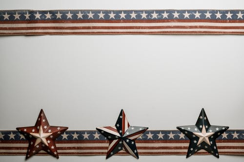 Star shaped souvenirs and ribbons with American flag pattern placed on white table