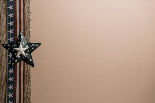 From above of star shaped badge placed on decorative ribbon with USA flag arranged on beige background