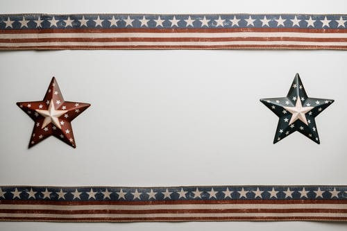 From above creative artwork with star badges and American flag ribbons attached to white surface