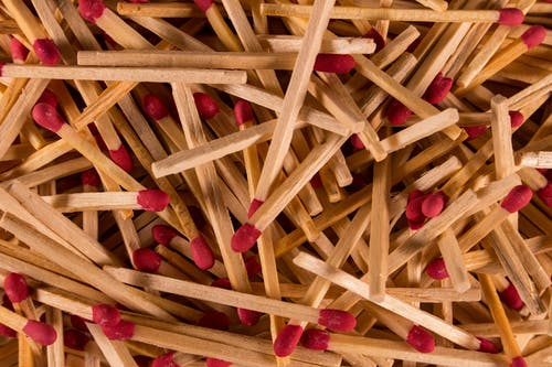 From above of pile of wooden matchsticks with red heads scattered chaotically as abstract background
