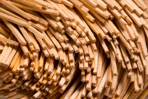 Closeup texture of stacked wooden thin sticks with uneven surface placed as abstract background