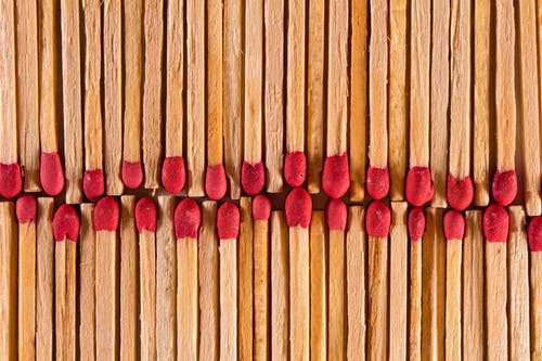 Top view of thin wooden matches with red flammable heads placed in rows as abstract background