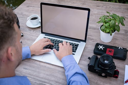 Person Using Macbook Pro Beside Dslr Camera