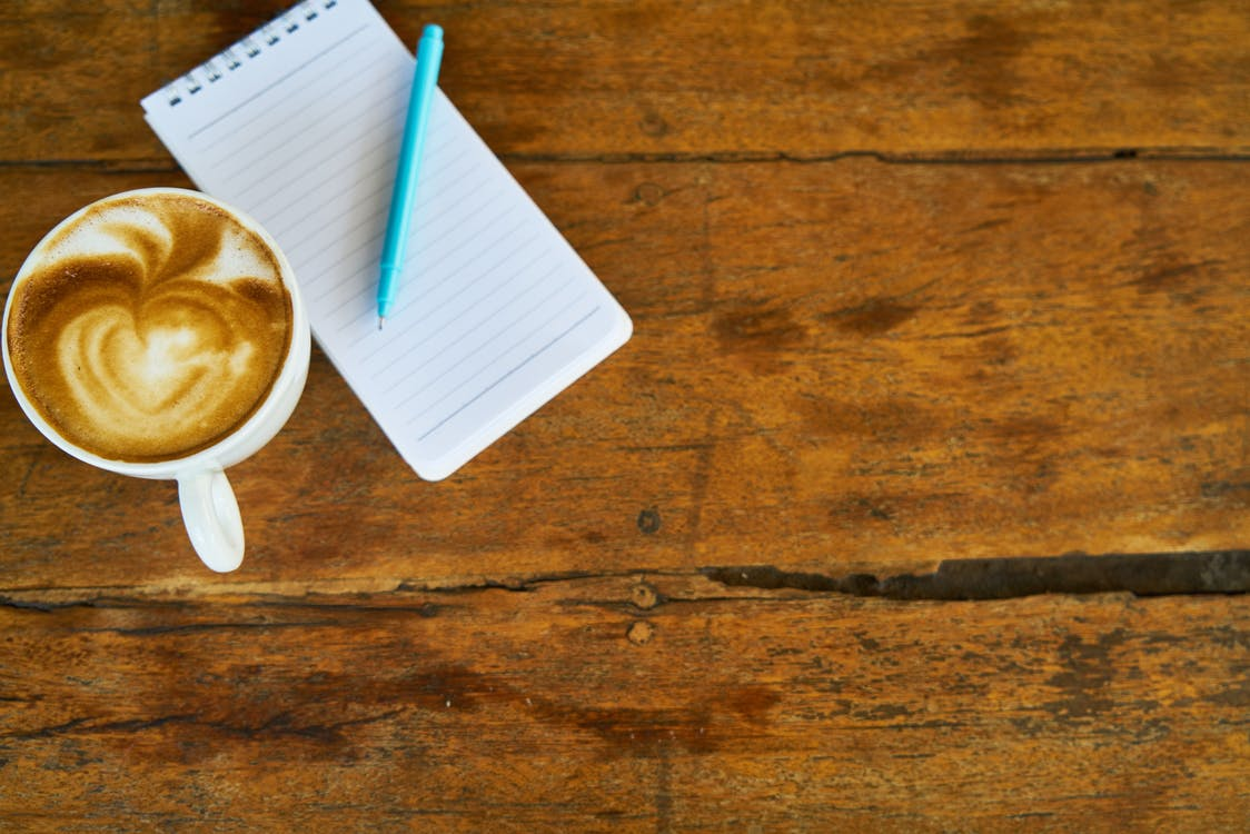 Coffee in Mug Beside Paper and Pen