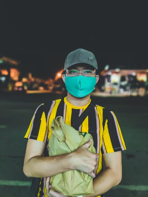Young male in protective mask glasses and cap holding shopping bag standing against luminous buildings at night