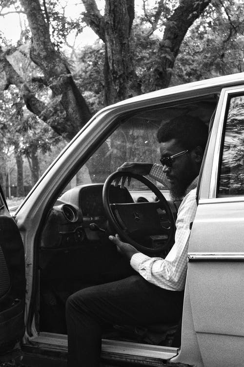 Bearded black male driver in old fashioned car