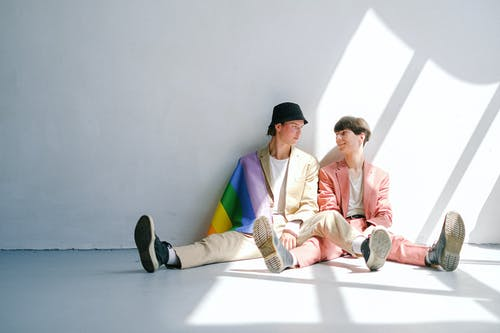 Two Men Sitting on the Floor with a Gay Pride Flag