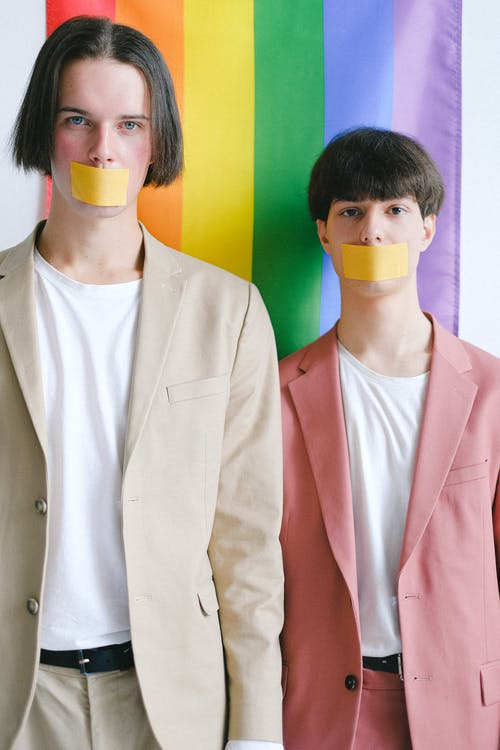 Two Men With Adhesive Tape Over Their Mouth