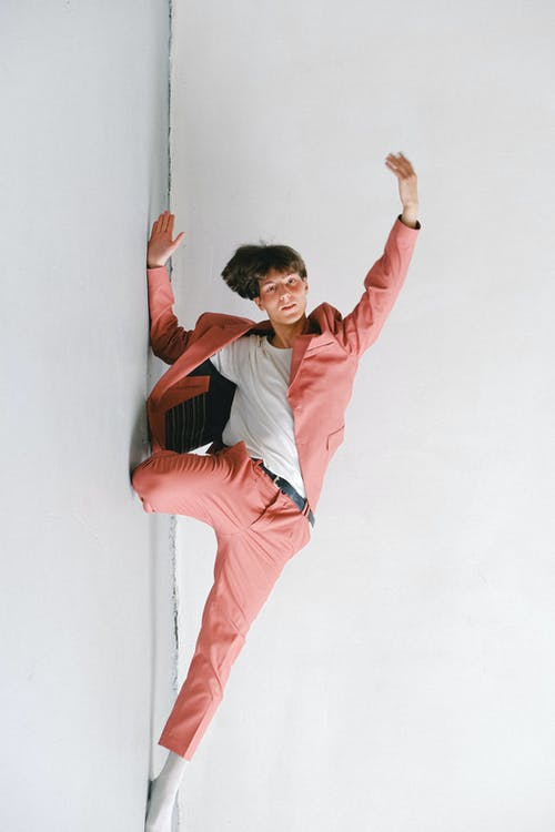 Man in White and Orange Long Sleeve Shirt and Pink Pants Jumping