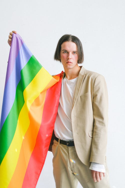 Woman in Beige Blazer Holding Multi Colored Flag