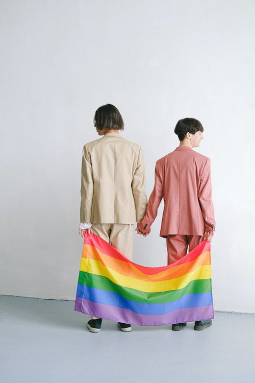 мужчины в костюмах с флагом гей прайда