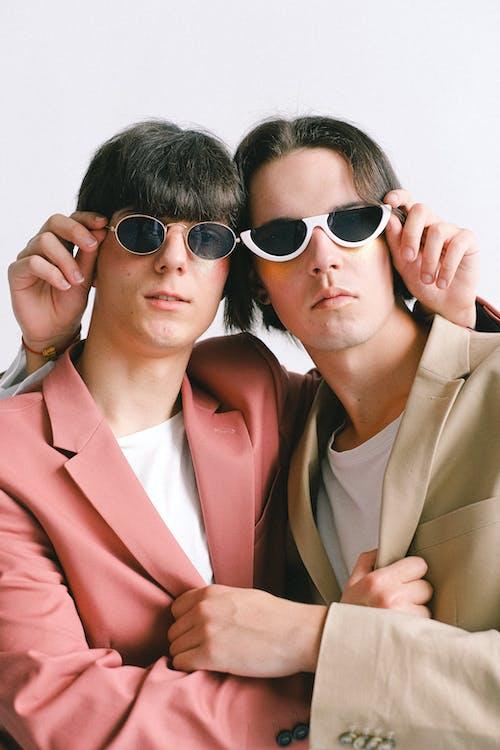 Woman in Brown Blazer Wearing Black Sunglasses Beside Woman in Brown Blazer