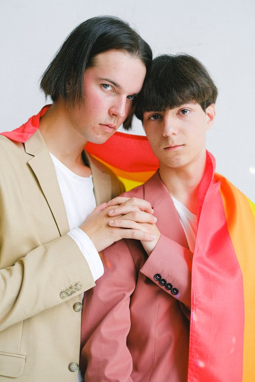 Two Men With a Gay Pride Flag Holding Hands