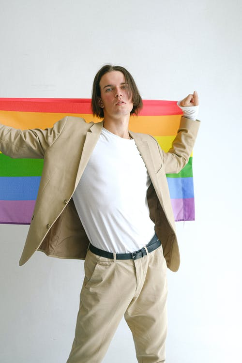 Man In Beige Suit Holding a Gay Pride Flag