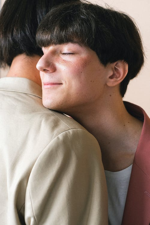 Man With his Eyes Closed Being Hugged